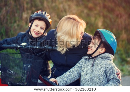 Mother teaching cycling kids outdoor at fall, little boy teeth smile - stock photo