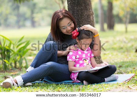 Mother teaching daughter for writing in the garden