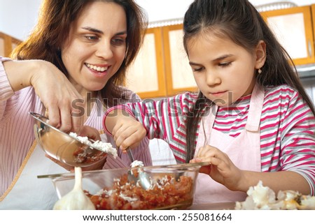 Mother teaching daughter how to prepare meat for lunch