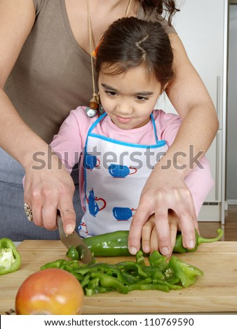 Mother teaching daughter to chop vegetables together in the kitchen using a chopping board and smiling. - stock photo