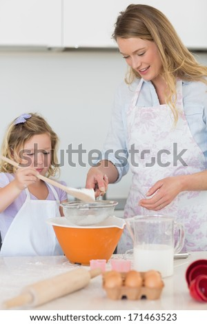 Mother teaching daughter to make cookies at kitchen counter