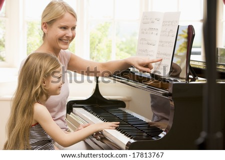Mother teaching daughter to play piano - stock photo