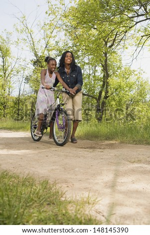 Mother teaching daughter to ride a bicycle