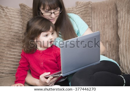 Mother teaching daughter with laptop