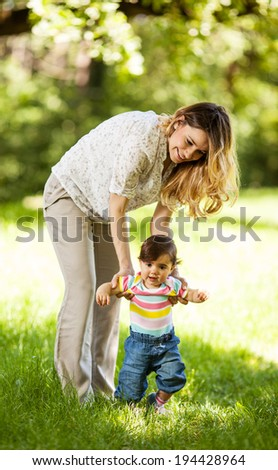 Mother teaching her baby to making first steps. - stock photo