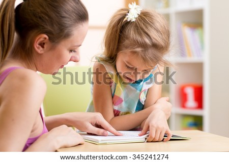 Mother teaching her child daughter to read - stock photo