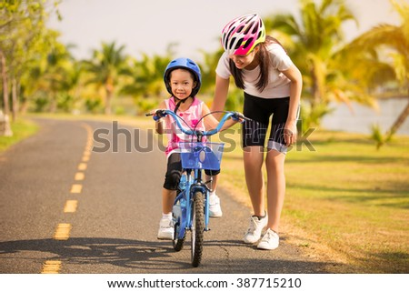 Mother teaching her daughter cycling  - stock photo