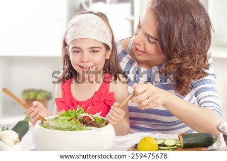 Mother teaching her daughter how to make a vegetable salad