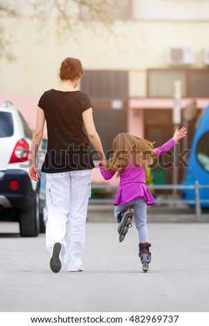 Mother teaching her daughter how to roller skate.