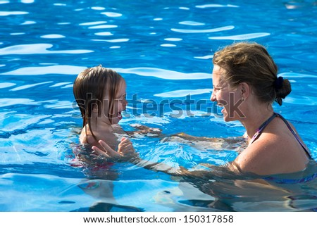 Mother teaching her daughter how to swim by how not to scare of water
