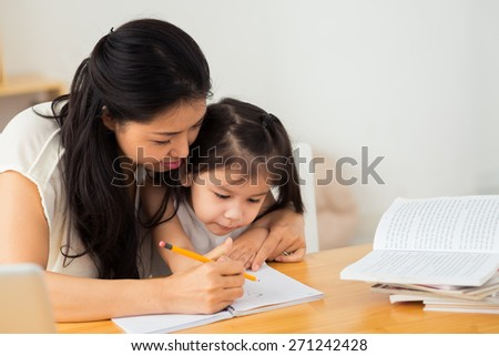 Mother teaching her daughter how to write - stock photo