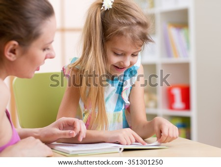 Mother teaching her kid daughter to read - stock photo