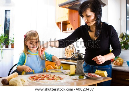 Mother teaching her little daughter how to cook pizza