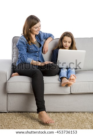 Mother teaching her little daughter working with a laptop
