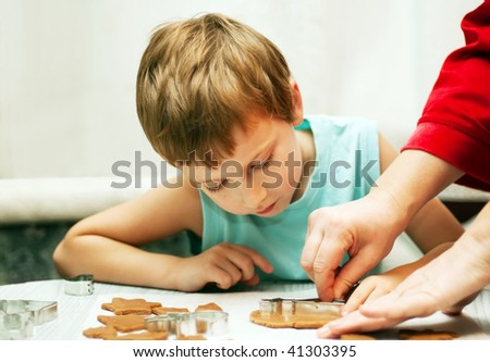 mother teaching her son to cut dough for christmas cookies