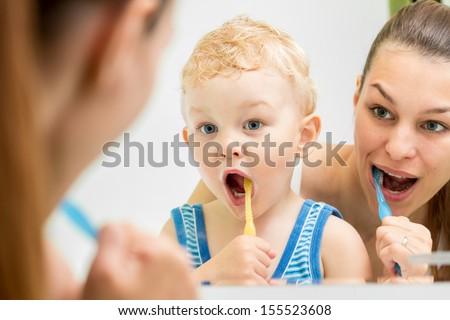 mother teaching kid teeth brushing - stock photo