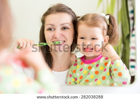 mother teaching kid teeth brushing in bathroom - stock photo