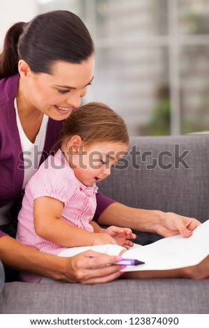 mother teaching little daughter drawing at home