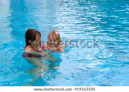 mother teaching little daughter to swim - stock photo