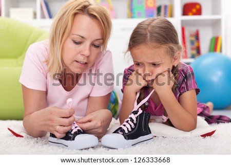 Mother teaching little unhappy girl to tie her shoes showing the process