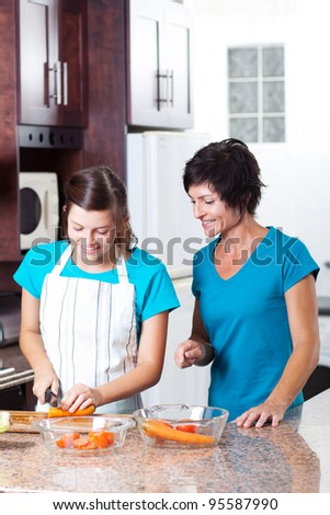 mother teaching teen daughter cooking in kitchen - stock photo