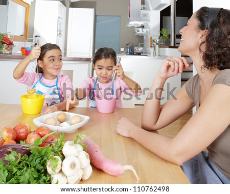 Mother teaching twin daughters to beat eggs in the kitchen, using whisks and having fun experimenting. - stock photo