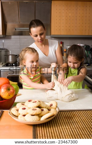 Mother teaching two little girls how to cook
