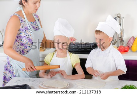 Mother teaching two young children, a girl and boy dressed in white chefs uniforms with aprons and toques, to bake in the kitchen showing them how to roll out dough for a homemade pizza base - stock photo