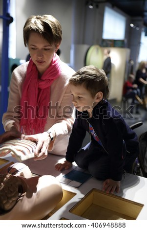 Mother telling her son about rib cage in museum - stock photo