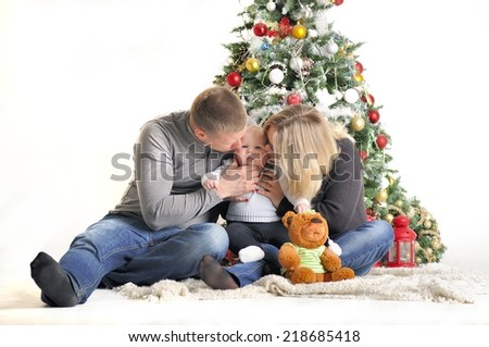 Mother, the father and their small child sits near Christmas tree - stock photo