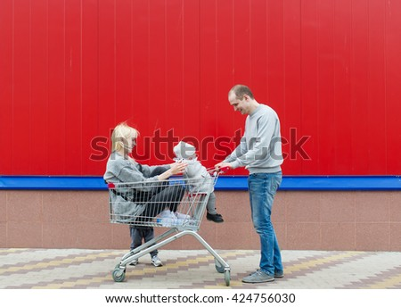 Mother, the father, children and the cart for food. They are at an entrance to a supermarket. - stock photo
