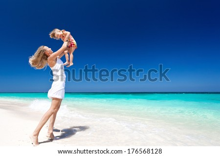 Mother throwing her daughter in air at the tropical beach - stock photo