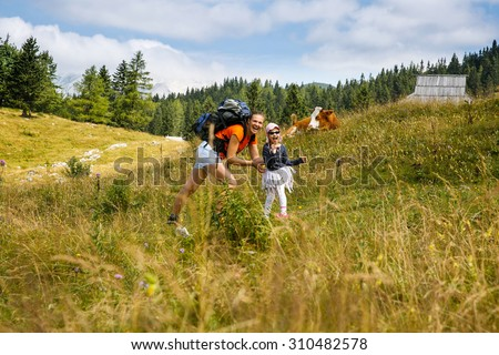 Mother tickling her daughter on mountain hike in the Alps, having fun, spending quality time together, with huts and cows in background. Active parenting, fun childhood and family bonding concept.  - stock photo