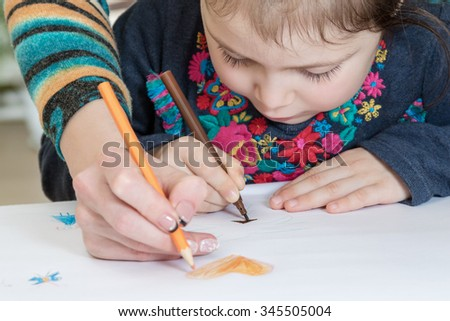 Mother together with a daughter draw on white paper close up - stock photo