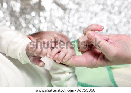 mother touch hand with newborn - stock photo