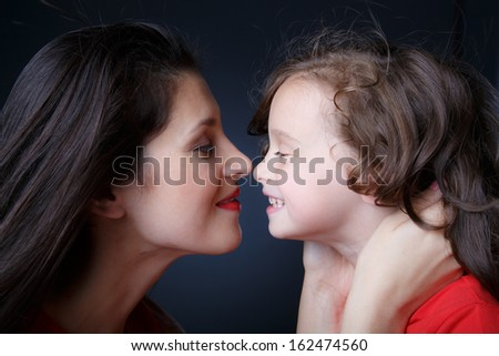 Mother touches nose to nose to her daughter - stock photo