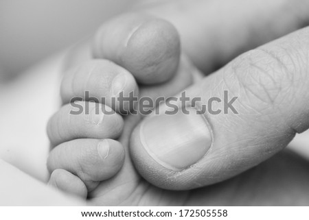 Mother touching baby's foot. Closeup. - stock photo