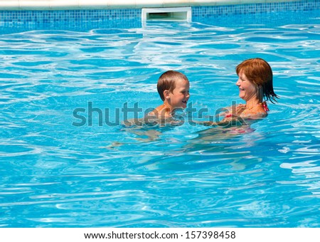Mother train her son to swim in the summer outdoor pool.