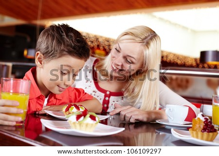 Mother treating her son to a delicious tart with cream and fruit