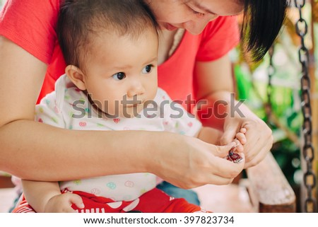 Mother try to nail cutting for her 7 months baby. - stock photo