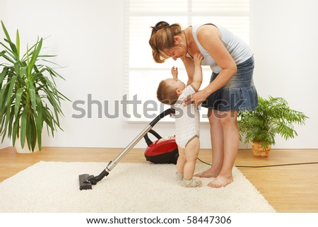 Mother trying to clean the floor while she's baby is crying and wants to be picked up - stock photo