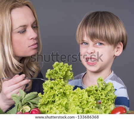 Mother trying to feed her little son who hates eating tomato - stock photo