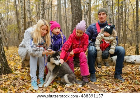 mother, two daughters, father and little boy sitting on fallen birch tree in forest, near Husky breed puppy