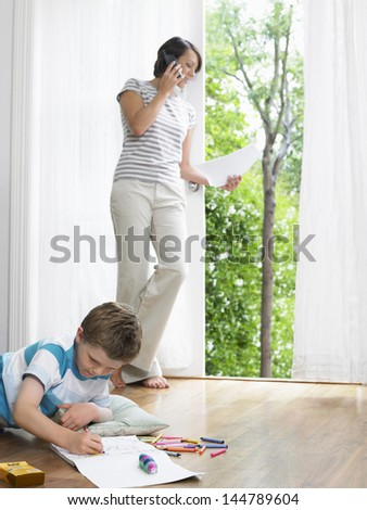 Mother using cellphone while son drawing on the floor - stock photo