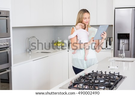Mother using digital tablet while carrying her baby in kitchen at home