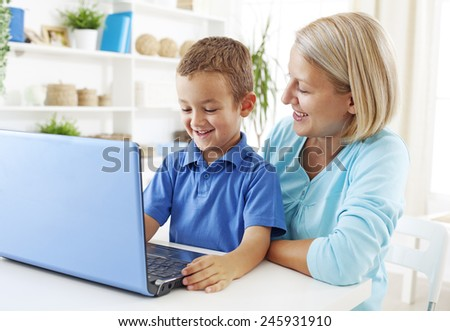 Mother using laptop with her son - stock photo