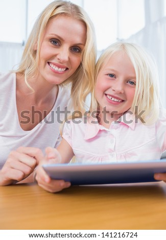 Mother using tablet pc in the living room with her daughter