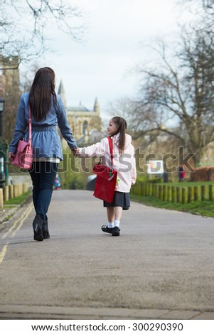 Mother Walking Daughter To School Along Path - stock photo