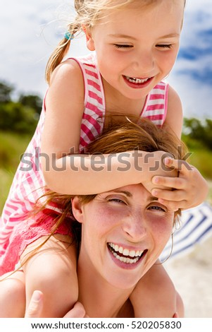 mother walking the beach with daughter