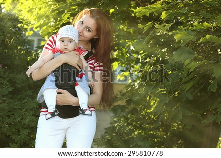 mother walking with a baby park sun trees - stock photo